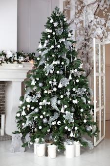 Festlicher weihnachtsinnenraum verziert mit weihnachtsbaum und geschenken. stilvoller wohnzimmerinnenraum mit verziertem weihnachtsbaum mit den bällen, girlande und kieferngirlande, die vom kamin hängen. neujahr