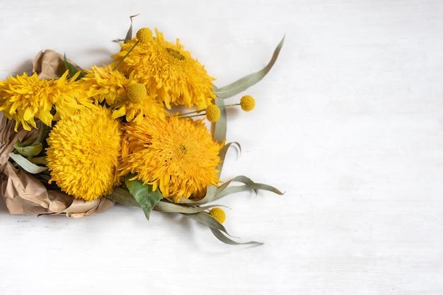 Festlicher weißer hintergrund mit sonnenblumen und craspediablumen, kopienraum.