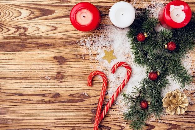 Festlicher winterhintergrund mit tannenzweigen, schnee und zuckerstangen auf holzbrett