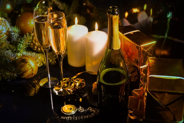 Festliches arrangement zum feiern des neuen jahres mit kerzen, champagner, tannenzweigen, weihnachtskugeln und geschenkboxen in goldenem glanzpapier verpackt