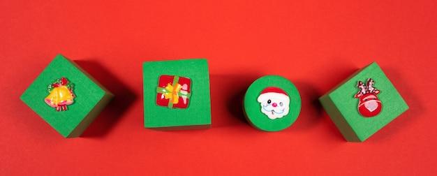 Festliches banner mit draufsicht vier grüne kuscheltierwürfel mit weihnachtssymbolen oben auf rotem hintergrund. weihnachtsdekorationen.