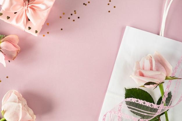 Festliches banner mit einer rose auf einem rosa tisch. draufsicht, flach liegen. speicherplatz kopieren.