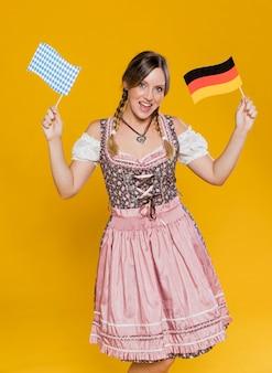Festliches bayerisches mädchen, das flaggen hält