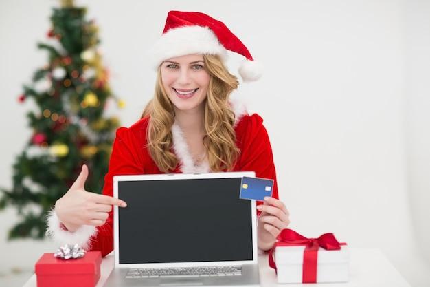 Festliches blondes online kaufend mit laptop und auf es zeigend