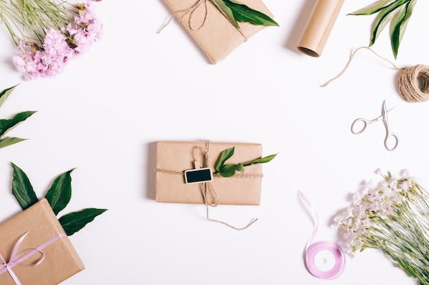 Festliches blumenarrangement auf weiß mit geschenkboxen