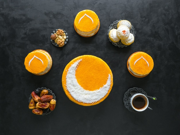 Festliches essen ramadan tisch. köstlicher hausgemachter goldener kuchen mit halbmond, serviert mit schwarzem kaffee und datteln. draufsicht