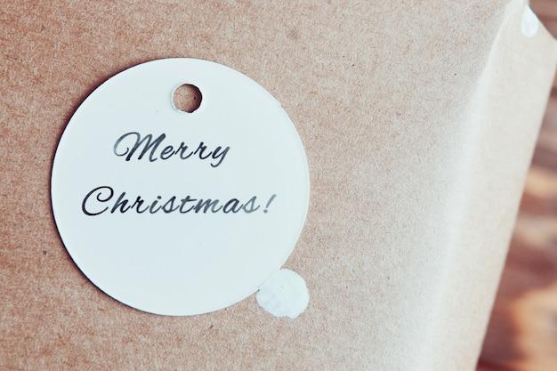 Festliches etikett auf kraftpapier mit weißen tupfen runder kartonanhänger mit frohe weihnachten-aufschrift...
