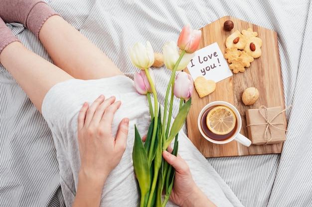 Festliches frühstück im bett zum valentinstag. tee und kekse mit eigenen händen in form von herzen. eine notiz auf papier, ein geschenk und blumen für ihr geliebtes mädchen.
