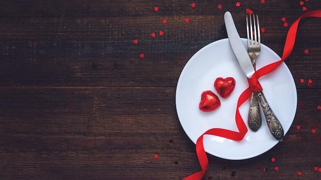 Festliches gedeck des valentinstags, flache lage mit zwei roten herzform-pralinen