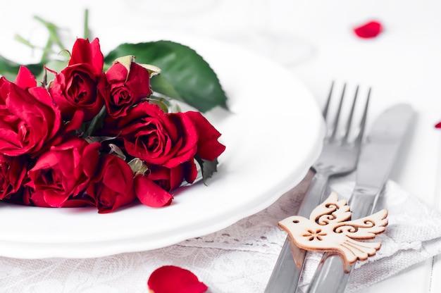 Festliches gedeck mit beige rosen, weingläsern, servietten und besteck