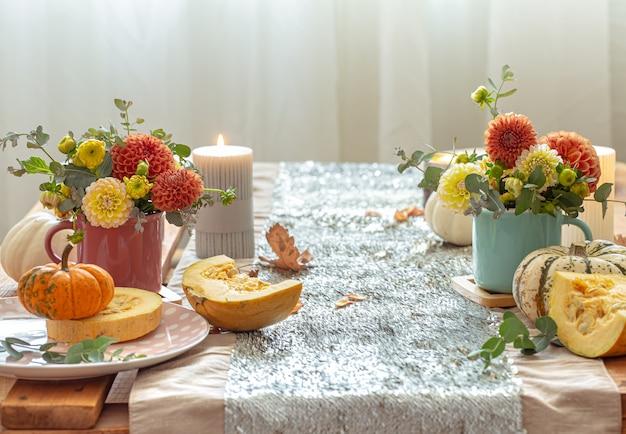 Festliches gedeck mit kürbissen und chrysanthemenblüten