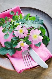 Festliches gedeck mit rosa blumen.