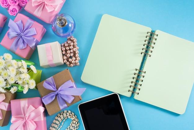 Festliches hintergrundkastengeschenksatinbandbogenblumenschmuckperlenotizbuchtabletten-hintergrundblau