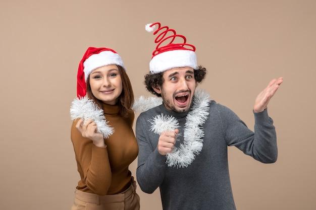 Festliches konzept der neujahrsstimmung mit aufgeregtem coolem paar reizendes paar, das rote weihnachtsmannhüte auf grau trägt