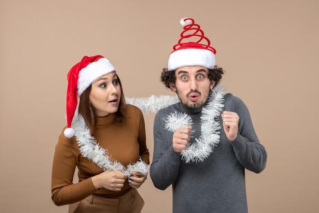 Festliches konzept der neujahrsstimmung mit aufgeregtem coolem reizendem paar, das rote weihnachtsmannhüte trägt, konzentrierte sich auf etwas auf grau