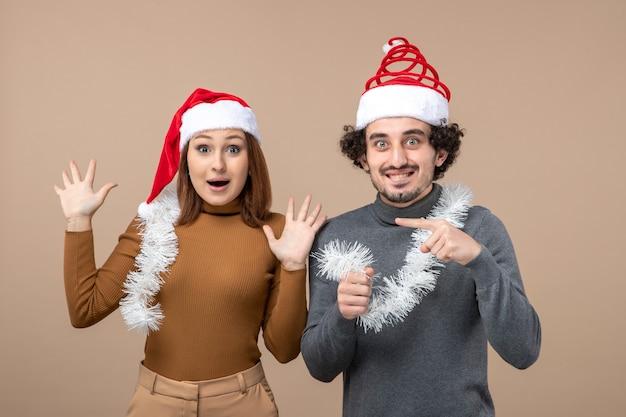 Festliches konzept der neujahrsstimmung mit aufgeregtem kühlem zufriedenem reizendem reizendem paar, das rote weihnachtsmannhüte auf grauem lagerbild trägt