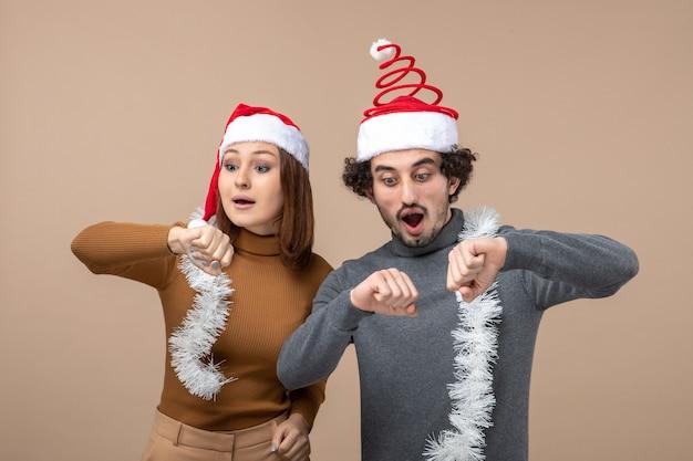 Festliches konzept der neujahrsstimmung mit aufgeregtem kühlem zufriedenem reizendem reizendem paar, das rote weihnachtsmannhüte trägt, die ihre zeit auf grau überprüfen