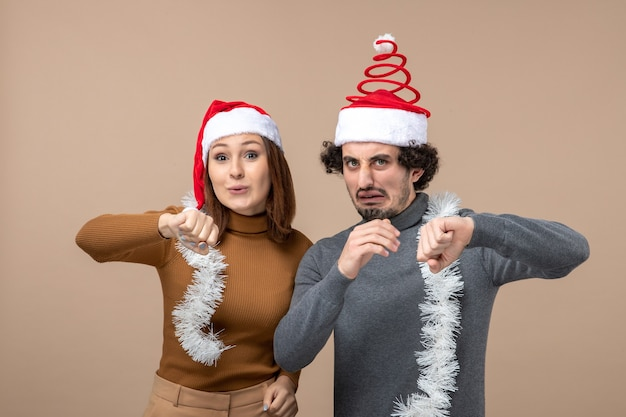 Festliches konzept der neujahrsstimmung mit aufgeregten kühlen zufriedenen reizenden reizenden paaren, die rote weihnachtsmannhüte tragen