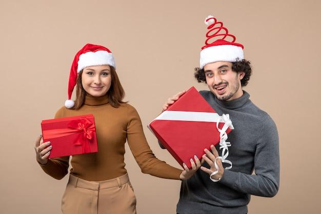 Festliches konzept der neujahrsstimmung mit coolem reizendem paar, das rote weihnachtsmannhüte auf grau trägt