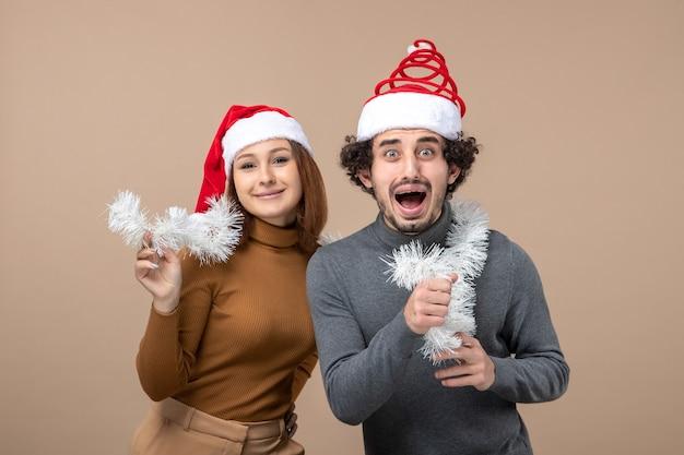 Festliches konzept der neujahrsstimmung mit dem kühlen reizenden paar, das rote weihnachtsmannhüte auf grauem bild trägt