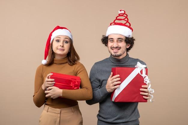 Festliches konzept der neujahrsstimmung mit dem kühlen reizenden paar, das rote weihnachtsmannhüte auf grauem foto auf lager trägt