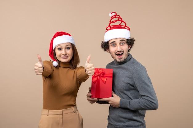 Festliches konzept der neujahrsstimmung mit dem lustigen zufriedenen glücklichen reizenden paar, das rote weihnachtsmannhüte auf grau trägt