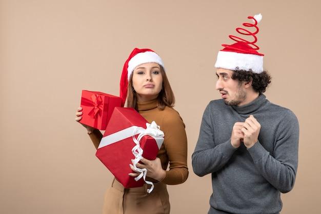 Festliches konzept der neujahrsstimmung mit lustigem coolem reizendem paar, das rote weihnachtsmannhüte auf grau trägt