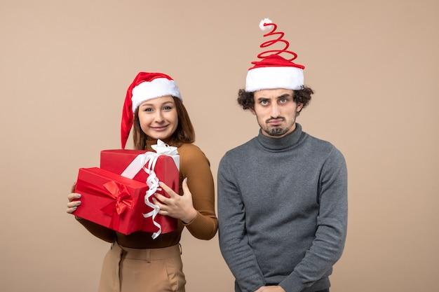 Festliches konzept der neujahrsstimmung mit lustigem coolem reizendem paar, das rote weihnachtsmannhüte auf grauem filmmaterial trägt