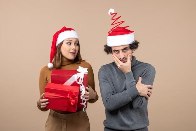 Festliches konzept der neujahrsstimmung mit lustigem coolem reizendem paar, das rote weihnachtsmannhüte trägt, die auf etwas auf grau fokussiert sind