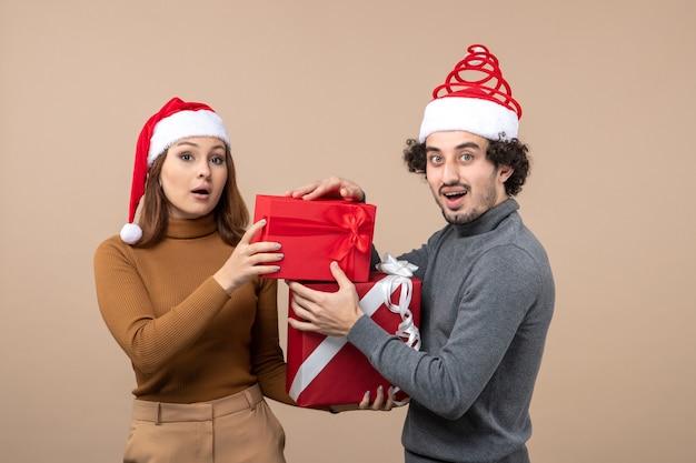 Festliches konzept der neujahrsstimmung mit lustigem glücklichem reizendem paar, das rote weihnachtsmannhüte-geschenkausstellungszeremonie auf grau trägt