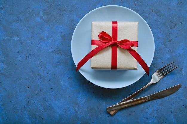 Festliches konzept. geschenk in handwerk öko-papier mit einem roten band auf blauem teller mit gabel und messer auf blauem hintergrund mit kopienraum.