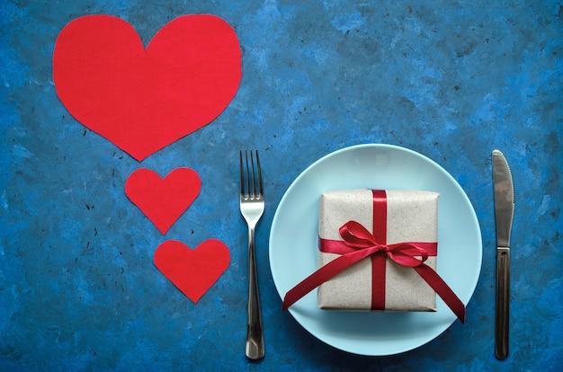 Festliches konzept. geschenk in handwerklichem öko-papier mit rotem band auf blauem teller mit einer gabel und einem messer auf einem blauen hintergrund mit herzen. geburtstag, valentinstag oder andere universelle grüße