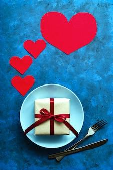 Festliches konzept. geschenk in handwerklichem öko-papier mit rotem band auf blauem teller mit einer gabel und einem messer auf einem blauen tisch mit herzen. geburtstag, valentinstag oder andere universelle grüße