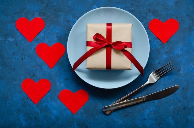 Festliches konzept. geschenk in handwerklichem öko-papier mit rotem band auf blauem teller mit einer gabel und einem messer auf einer blauen oberfläche mit herzen. geburtstag, valentinstag oder andere universelle grüße