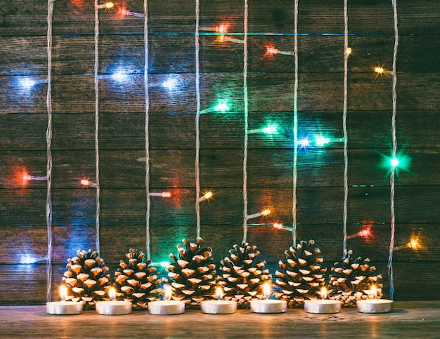 Festliches neujahrs- und weihnachtskonzept. mehrfarbige weihnachtslichtgirlande, tannenzapfen und kerzen auf dem hintergrund von alten scheunenbrettern