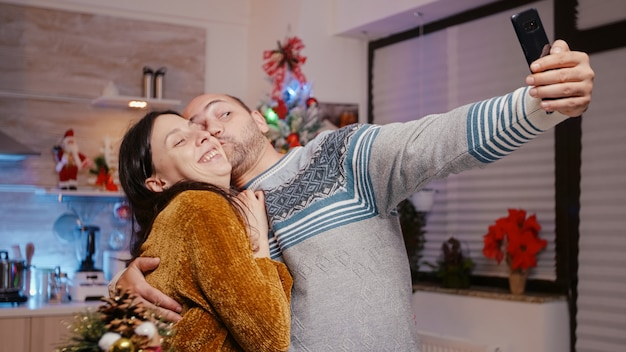 Festliches paar, das fotos auf dem smartphone macht und sich fröhlich fühlt