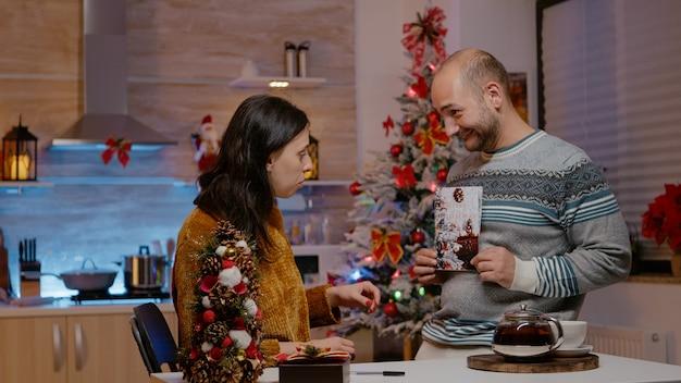 Festliches paar, das weihnachtskarte für feiertagsfest unterschreibt
