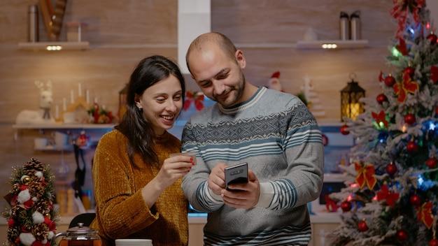 Festliches paar kauft geschenke mit kreditkarte auf dem smartphone