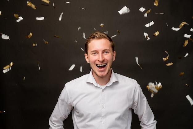 Festliches porträt. lustige feier. amüsierter mann, der im konfettiregen lächelt, der auf schwarzem hintergrund lokalisiert wird.