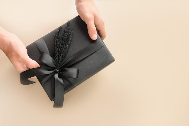 Festliches schwarzes geschenk mit dekorationen in der hand zum vatertag. schwarzer freitag.