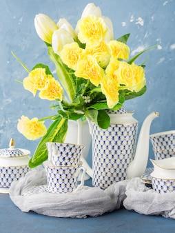 Festliches set der ostern-teeparty und gelbe blumen
