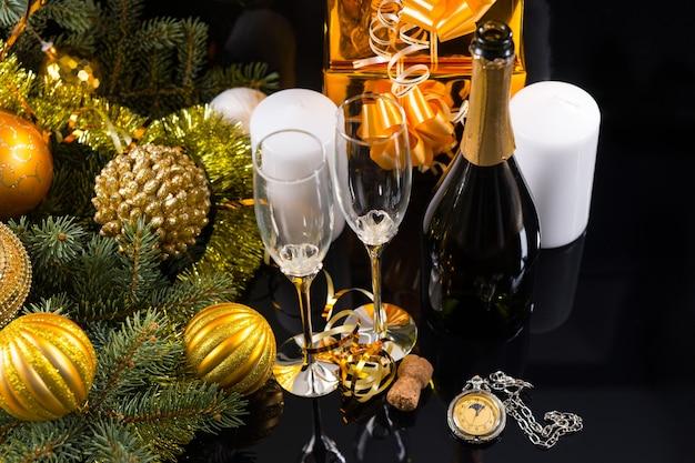 Festliches stilleben mit hohem winkel - nahaufnahme von eleganten champagnergläsern auf schwarzem hintergrund mit taschenuhr, weißen kerzen, goldenen geschenken und immergrünem dekor mit weihnachtskugeln und lametta