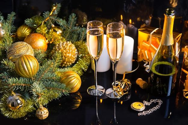 Festliches stilleben mit hohem winkel - zwei gläser prickelnder champagner mit flasche, kerzen, geschenken, taschenuhr und weihnachtsschmuck auf schwarzem hintergrund