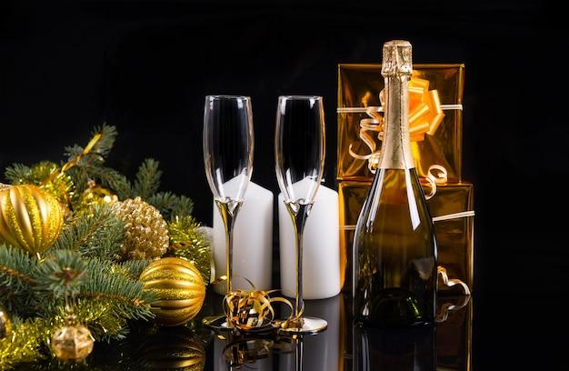 Festliches stillleben - flasche champagner mit eleganten gläsern auf schwarzem hintergrund mit geschenken, kerzen und dekorierten evergreens mit weihnachtskugeln und lametta