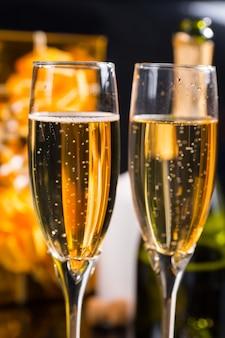 Festliches stillleben - gläser gefüllt mit prickelndem champagner vor schwarzem hintergrund mit goldverpackten geschenken und weißen kerzen