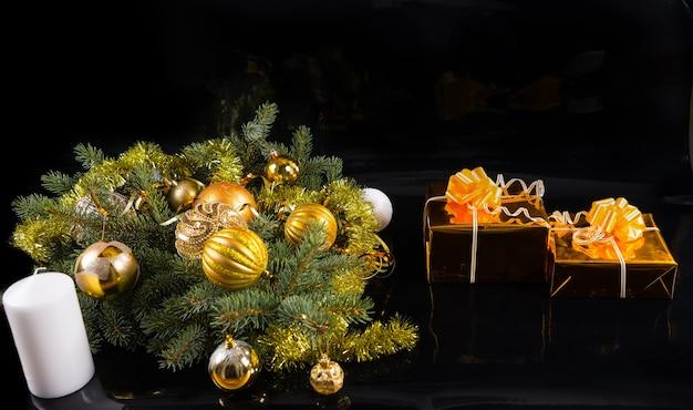 Festliches stillleben - paar in gold verpackte geschenke mit schleifen auf schwarzem hintergrund mit weißer kerze und immergrünen zweigen, verziert mit weihnachtskugeln und goldener lametta-girlande mit textfreiraum