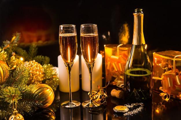 Festliches stillleben - zwei gläser prickelnder champagner mit flasche, kerzen, geschenken, taschenuhr und weihnachtsschmuck auf schwarzem hintergrund in warmer beleuchtung