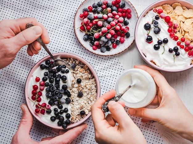 Festliches und gesundes frühstück für die liebsten. vintage schalen, cornflakes, müsli, joghurt, frische beeren und hände eines jungen paares.