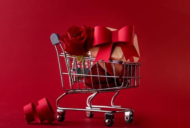 Festliches verkaufskonzept-banner des valentinstags mit geschenkbox-rose und roten papierherzen im einkaufswagen gegen ein rot.