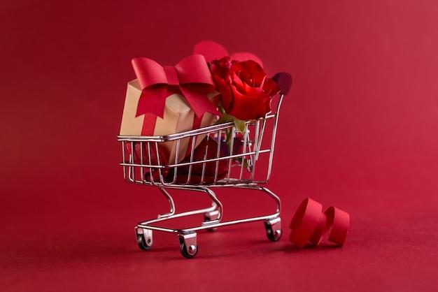 Festliches verkaufskonzept des valentinstags mit geschenkboxrose und roten papierherzen im einkaufswagen gegen ein rot.